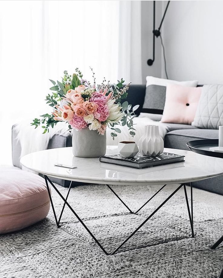 White marble coffee table with flowers and grey couch