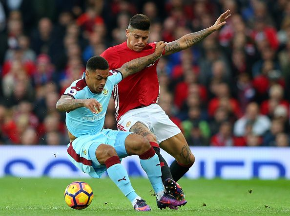 Andre Gray of Burnley and Marcos Rojo of Manchester United battle for possession during the Premier League match between Manchester United and...