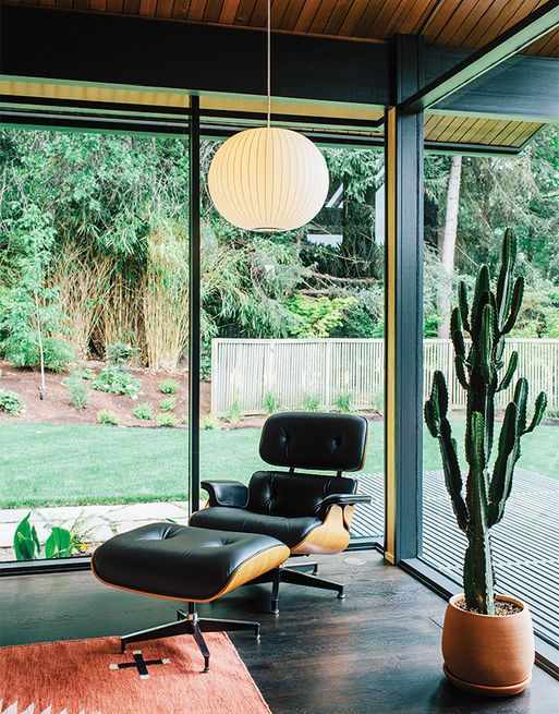 In true mid-century fashion, a George Nelson Bubble Lamp is paired with an Eames Lounge by Charles and Ray Eames in a corner of a living room kitted out by interior designer Jessica Helgerson. The glass walls and mitered corner are original features of architect Saul Zaik's 1956 design.