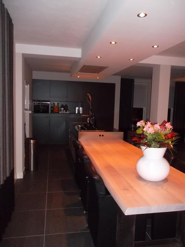 Keuken met kastenwand in bouwkundige nis en greeploos eiland met robuust RVS werkblad doorlopend in een massief eiken eettafel — in Maarheeze.