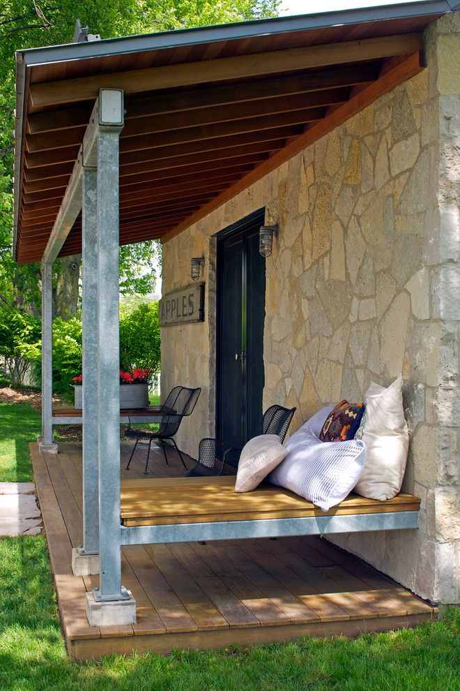 eclectic front porch idea floating wood daybed a pile of accent pillows natural stone exterior walls wood board floors without finishing of Add A Comfort Zone in Your Front Porch with These Fabulous Front Porch Seating Ideas