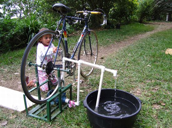 DIY - water pump.  Like the merry-go-round water pump.  This would need a storage tank.  You could get kids to ride the bike all day long pumping water for the community.  Brilliant.