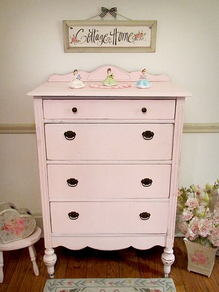 This antique dresser has been refinished and painted in a soft pink and distressed. The piece features four dovetail constructed drawers, original hardware, original wheels, and pretty curves on the backboard and along the bottom of the piece. Perfect for any shabby chic home or little girl's bedroom.