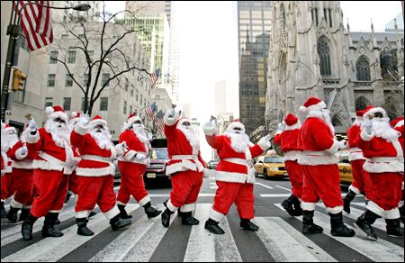 A huge group of Santa Clauses cross Fifth Avenue, NYC during SantaCon which usually occurs the week before Christmas.
