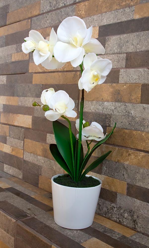 Arreglo floral artificial para interiores. Orquídea blanca con maceta, un elemento de decoración para el hogar.
