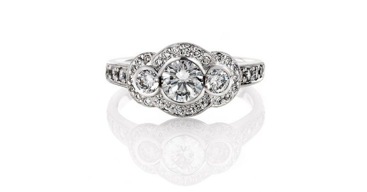 Art Deco style Ring. Round brilliant cut diamonds surrounded by small pave set diamonds in 18ct white gold