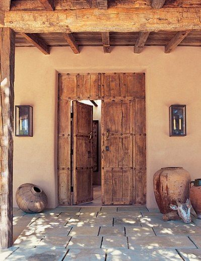 Los Angeles-based interior designer Martyn Lawrence-Bullard created an adobe in Santa Fe for art gallery owner Allene LaPides and her husband, Jerry.Flanking the entrance are an Indian gourd and a 19th-century French oil jar.