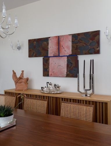 """Encontrar o lugar certo para um quadro também é sinônimo de estudo das proporções. A pintura marrom e rosa por ser mais alongada pôde ser pendurada sobre o bufê, pois acompanhava seu comprimento. Além disso, não """"roubava a cena"""" das 19 obras de Portinari, na mesma sala de jantar, dispostas em duas paredes (fotos 3 e 5)"""