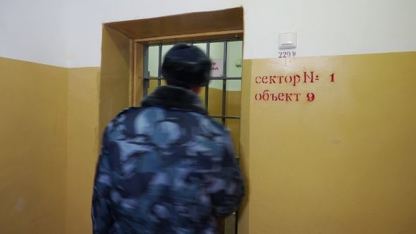 Prison Officer Walking in Corridor of Russian Penitentiary Colony