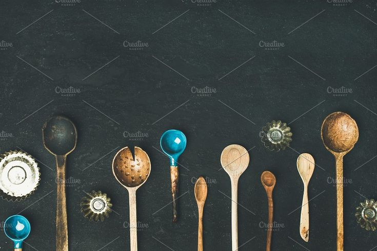 #Various vintage kitchen spoons  Flat-lay of various old vintage kitchen spoons and baking tin molds over black stone background top view copy space horizontal composition. Rustic cooking concept