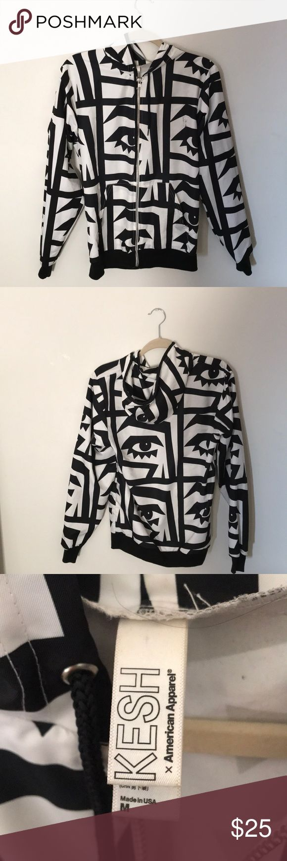 American Apparel zip up wind breaker Black&White eye pattern zip up wind breaker with hood size (M) USA Hardly ever worn but does have have black stain but was there when I purchased the jacket you can see it in the fourth photo. It blends in with the design so you can't really tell American Apparel Jackets & Coats Puffers