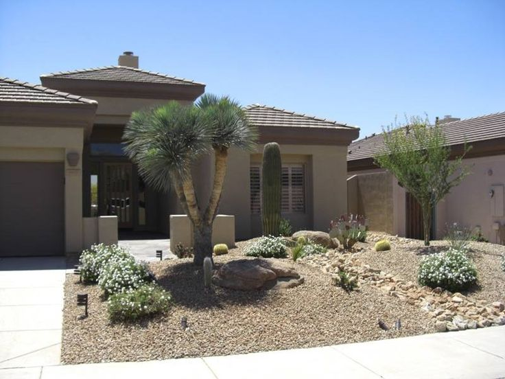 A dry creek bed comes from down the side of the house and splits this front  yard  breaking up the sea of gravel  The plantings and rock feature als. A dry creek bed comes from down the side of the house and splits