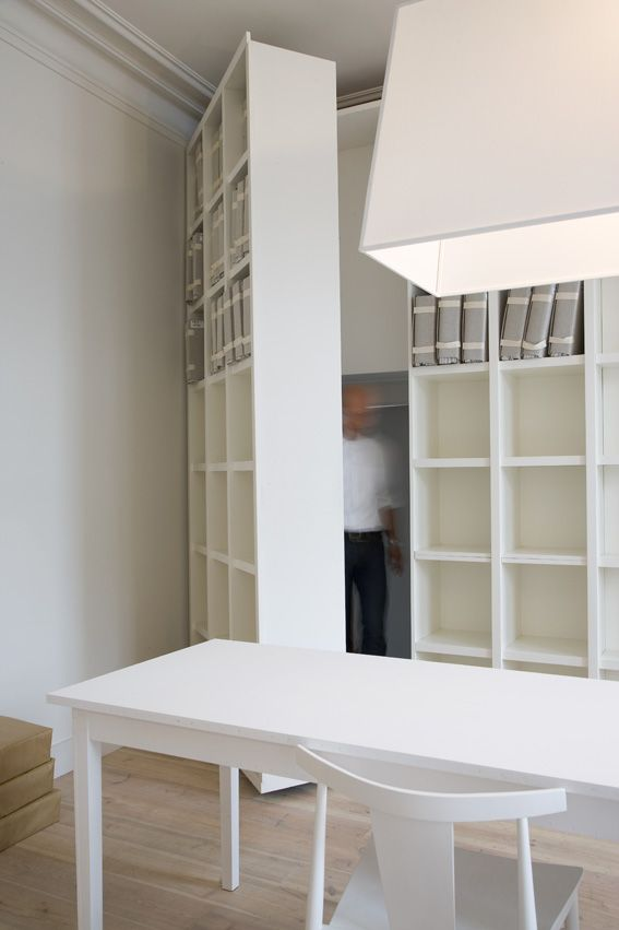 Floor to ceiling shelf doors for closet gives small workspaces more storage. by  Bieke Claessens. These are so cool!!! I love hidden closet/ shelf doors.