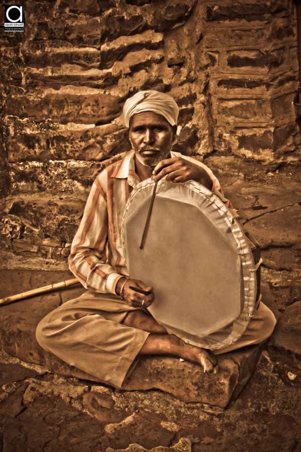 "A old man playing ""Tasha"" (One of the kind of drum instrument) at temple."