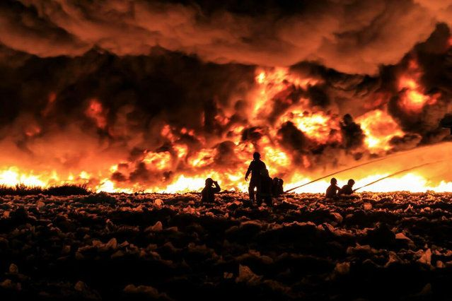 Fire fighters tackle a large blaze at a recycling centre in Smethwick, near Birmingham, central England July 1, 2013 in a handout picture provided by the West Midlands Fire Service. The fire service said they suspected the blaze was started when a Chinese lantern, a collapsible paper lantern lit by a candle, drifted into the centre which holds 100,000 tonnes of recycled paper and plastic. Up to 200 firefighters and 40 fire engines have been deployed. (Photo by Reuters/West Midlands Fire…