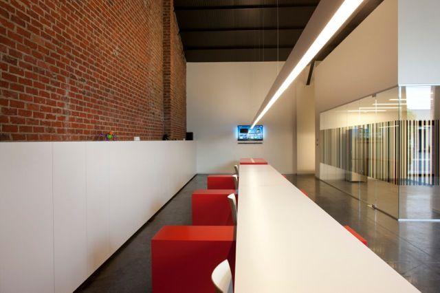 Lang wit bureau met rode stoelen - loft met bakstenen muur