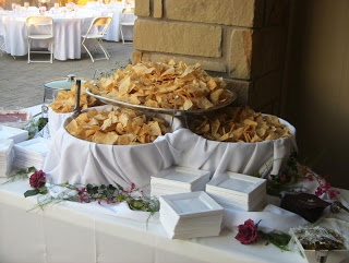 Nacho bar...chips in bog bowls draped with fabric (probably a tablecloth)…