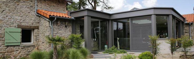 extanxia, véranda concept alu, vue extérieur avec mur en pierre et véranda en angle et puits de lumière