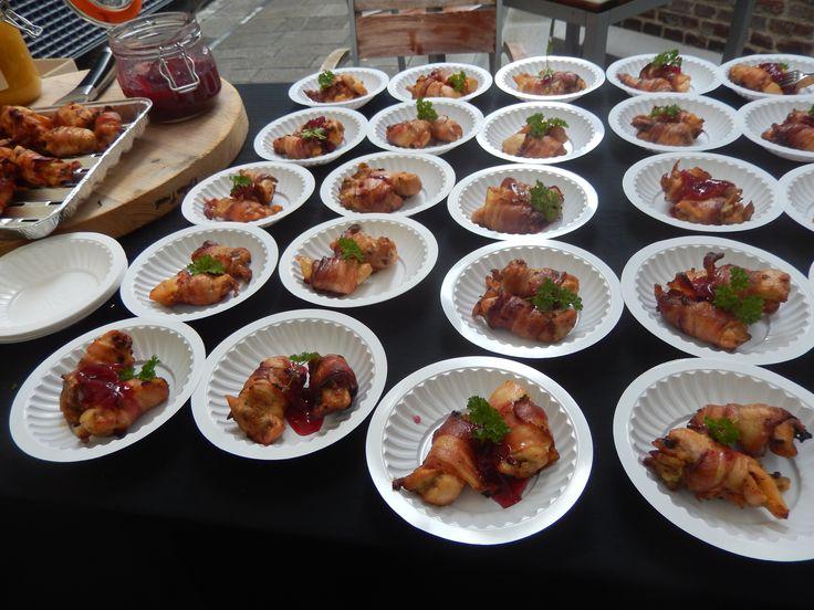 Kipdijtje omwikkeld met bacon. Op het bordje een chutney van rode ui en framboos erbij.