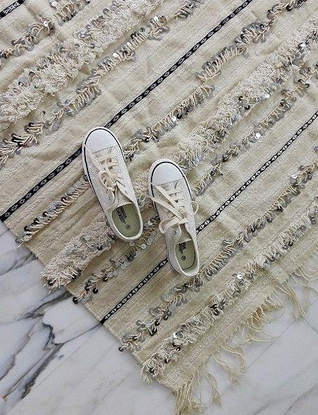 Bellissima handira vintage, la tradizionale coperta nuziale berbera, che può essere usata oltre che come coperta, anche come tappeto, per vestire un divano o appesa al muro per decorare una parete, apportando un tocco di raffinatezza e glamour in ogni ambiente. Realizzata a mano dalle popolazioni berbere dell'Alto Atlante in Marocco, è in lana e cotone e decorata con paillettes in metallo che scintillano e con il movimento producono un dolce suono