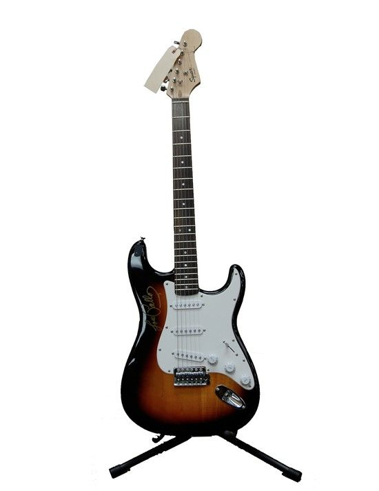 """Title: Fender Squire Bullet Sunburst Solid Body Electric Guitar with Lou Pallo autographed on body Mahwah Museum Number:    2014.06.039 Description:  Fender Squire Bullet Sunburst Solid Body Electric Guitar-autographed by Lou Pallo on the body Size:  12"""" W x 39"""" L x 2 1/2"""" D Year:                           unknown Market Price: $1,000, Starting Bid: $500"""