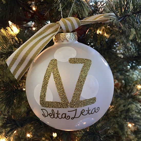 (DZ) Delta Zeta - Glitter Gold Ornament:  The Delta Zeta Gold Glitter Ornament is a must-have for any stylish sorority woman. With its classic white stripe ribbon and sparkly gold greek lettering, this ornament is the perfect holiday gift.  Comes packaged in a coordinating gift box for perfect present presentation.