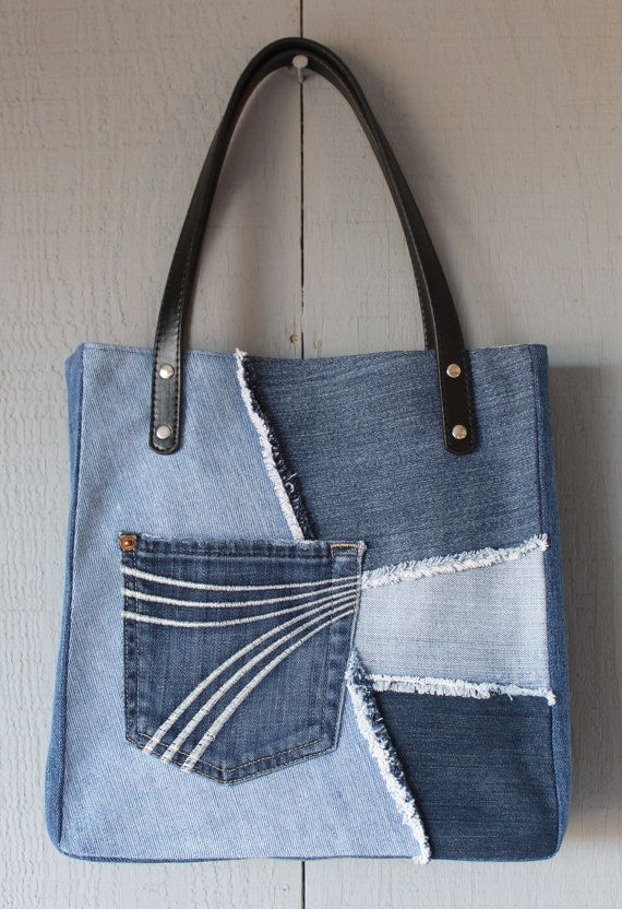 This is a handmade denim upcycled tote bag lined with a kaleidoscope inspired canvas with two interior pockets. This tote has two leather straps with two rivets on each side for secure handles. Additional pocket removed from jeans and sewn onto front, great for phone, keys, etc.  Dimensions: 11 (W) x 121/4 (H) x 2 1/2 (D) The straps are 22 Long with a 6 1/2 drop  Please feel free to contact me for custom orders.  Thank you.