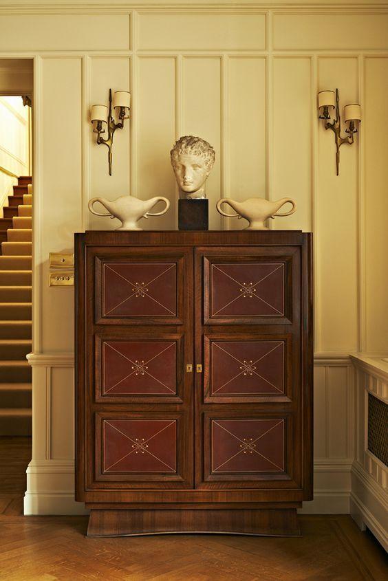 Dans l'entrée, le cabinet rouge de Maxime Old est encadré de deux appliques de Félix Agostini. Dessus, une tête d'Antinoüs, datant du xixe, et deux vases réalisés vers 1930 par Constance Spry pour les Ateliers de Fulham.: