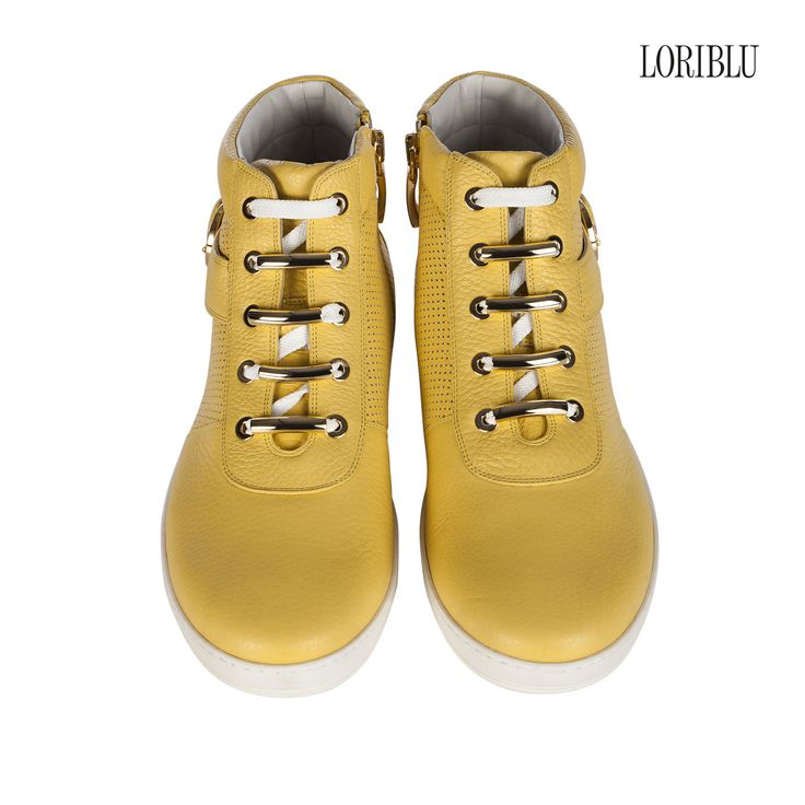 Yellow calfskin sneaker, with the glam touch of the decorative side strap and gold metal details.