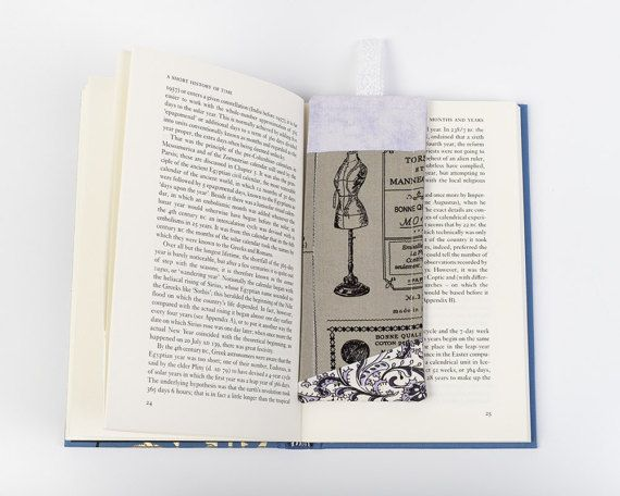 Beautiful fabric bookmark made using a patchwork technique. The front is made using grey and grey purple and the print features a tailors dummy. The back is made of sturdy light grey linen, and there is a cute lace tag at the top so you can easily see where you are up to in your book without damaging the pages.  This bookmark measures 17cm x 6.5cm, and the lace tag measures 4cm x 1.5cm.  Ideal gift for a book lover and/or sewers!    HANDMADE ITEMS: Whilst every effort is made to make per...