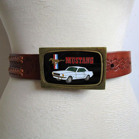 """60s Ford Mustand black and white enamel picture on solid brass belt buckle with Running horse Logo and Red, White and blue stripes. Attached to Brown leather tooled belt, with snaps to detach from buckle. Has eye like design with woven leather textured belt. Buckle Length: 3 1/8"""""""