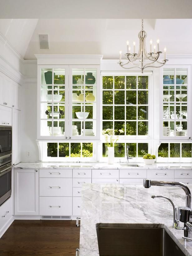 - 79 Beautiful Kitchen Window Options and Ideas on HGTV -- huge kitchen window has two backless cabinets with glass doors and shelves - store your pretties and keep the gorgeous view beyond!