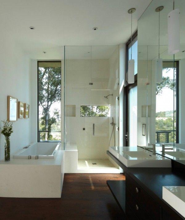 bath lies lengthwise next to frameless shower. Tall, narrow window to ceiling behind bath