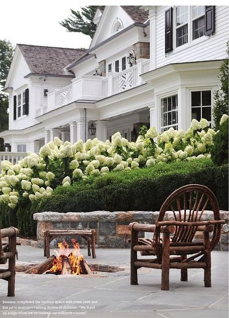 gorgeous white house with white hydrangeas and firepit