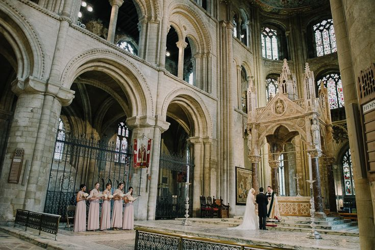 Suzanne Neville Lace 'Antonia' Wedding Dress and Jenny Packham Bridal Accessories for a traditional wedding ceremony in Peterborough Cathedral and a reception at Stapleford Park. Bridesmaids wear pale pink dresses and Groomsmen in tails.
