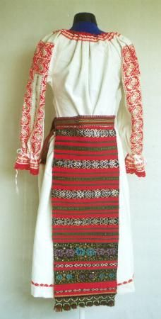 Romanian Women's costume from Maieru, Rodna valley, Bistriţa-Năsăud The underskirt (poale) has a row of red embroidery above the hem. Front and back aprons (catrinţe) made of a single width of red felted woollen material with black woven strips decorated with wide silver, and gold thread (beteala) two black woven horizontal stripes with multicoloured floral embroidery, and with a  row of green crochet lace on the hem Narrow woven fabric belt (brâu) woven in stripes of red, yellow and green