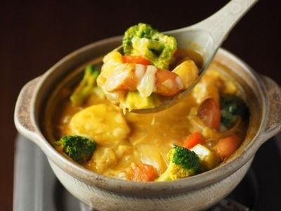 チーズカレー鍋  土鍋にじゃがいも、にんじんなどの野菜と、コンソメスープ、豆乳、カレールー、ウインナーを順に加えます。仕上げにカレー粉とチーズをプラスして、コクまろ仕立てに。
