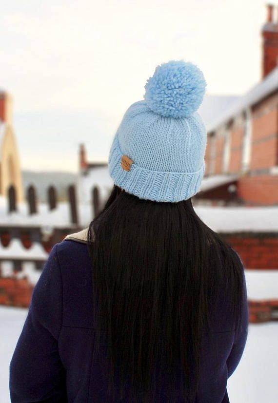 Unique one off handknitted bobble hat in baby blue. Each piece is knit by hand in our North Wales studio so every hat is unique. Finished with a Junkbox Ultraleather tag. Wool/Acrylic blend. Unisex style. One size fits all. THE Winter accessory!!! (Co-ordinating items are available)