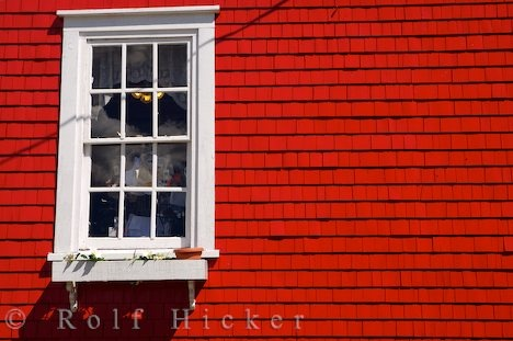 Window Lunenburg Outfitting Co Nova Scotia: A window with a light shining inside stands out against the red wall of the Lunenburg Outfitting Co building situated in the town of Lunenburg in Nova Scotia, Canada. The window of the Lunenburg Outfitting Co building stands out stark white against the red background of the building in the town of Lunenburg, in the Lunenburg Harbour along Lighthouse Route, Highway 3 in Nova Scotia, Canada. Lunenburg was established in 1753 and is an old community…