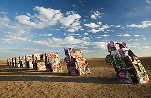Just west of Amarillo, Texas, 10 sets of graffiti-covered tail fins stand as a tribute to the American dream. The art installation, known as Cadillac Ranch, features 10 classic cars, half buried nose...