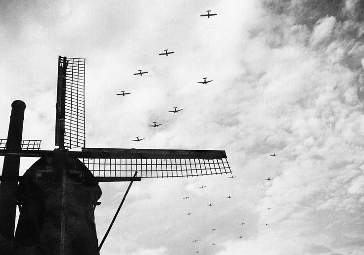 In the sky above the Netherlands, american tow planes with gliders strung out behind them fly high over a windmill in Valkenswaard, near Eindhoven, on their way to support airborne armies in Holland on Sept. 25, 1944.