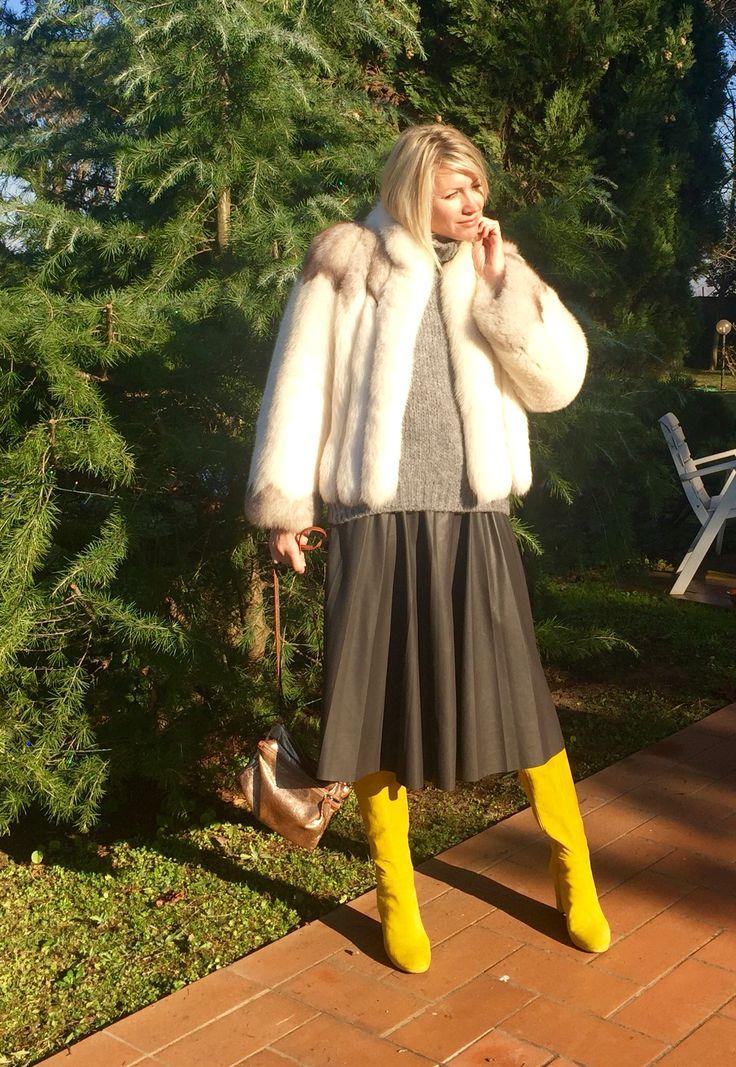 Stivali gialli, gonna di pelle, giacca di pelliccia