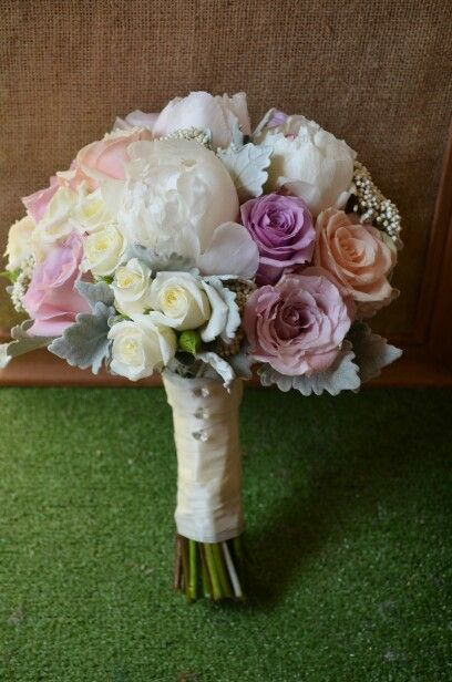 Fragrant Peonies are nestled amongst roses in an elegant Bridal Bouquet