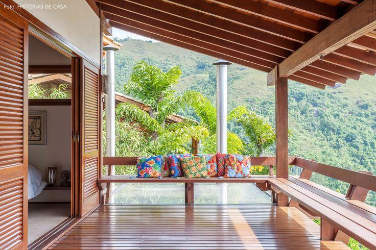 Essa varanda tem um grande banco de madeira que faz parte da estrutura da casa. Para completar a decoração, almofadas com estampas de chita.