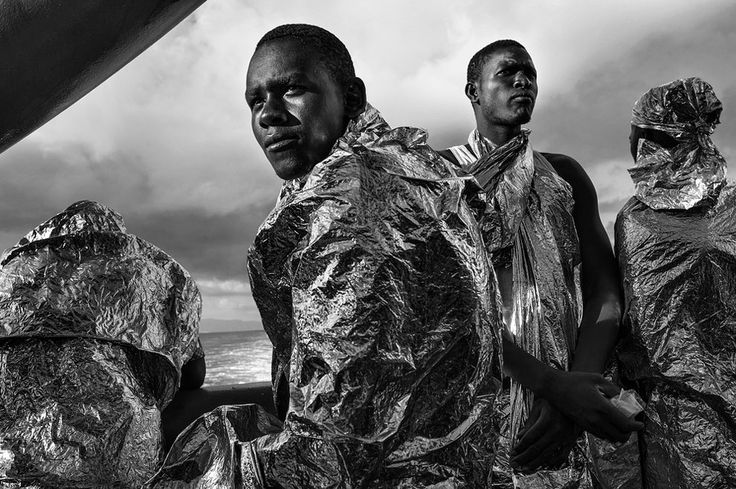 After spending two days and two nights on the deck of the Doctors Without Borders search-and-rescue ship Bourbon Argos, rescued migrants - still wrapped in their emergency blankets - catch sight of the Italian coast for the first time soon after dawn.  Francesco Zizola - August 23, 2015