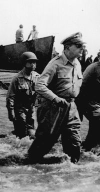 General Douglas MacArthur wades ashore during initial landings at Leyte.  October, 1944