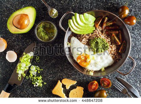 Breakfast of Eggs, Avocado, salad of Tomatoes, Pesto and buckwheat in a frying Pan on the table