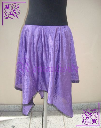 Falda plato irregular de tafetán, con detalle de puntilla.