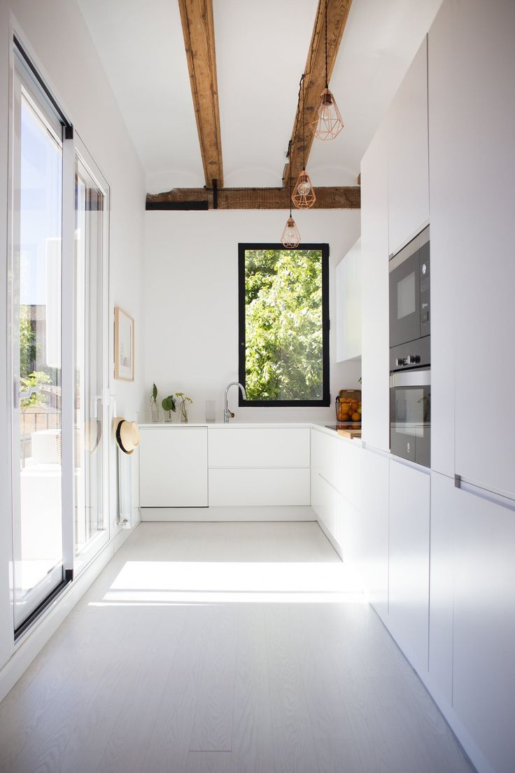 White modern kitchen with exposed beams