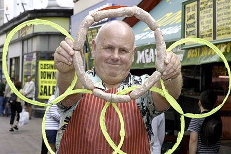 A butcher whose harbourside shop will look out over the 2012 Olympic sailing events has been ordered to remove a sign of the Olympic rings made from sausages.